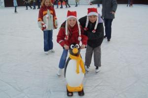 Kinder mit Lernpinguin auf dem Eis - Eisbahn am Dobben