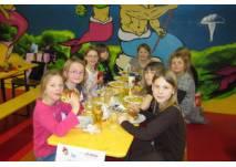 Kinder am Geburtstagstisch im Indoor-Spielplatz