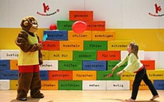 Kind und Maskottchen Taffi beim Deutschen Turnfest 2013