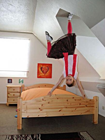 Kind macht Handstand auf der Bettkante