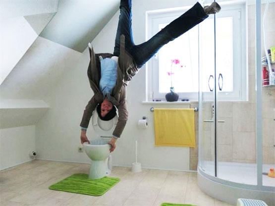 Junge macht Handstand auf der Toilette