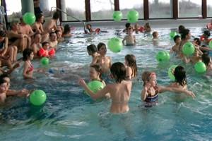 Kinder mit Luftballons im Hallenbad