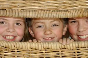 Kinder schauen aus der Korb-Schaukel