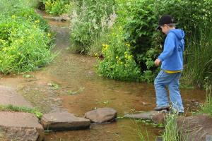 Kind läuft über einen Bach