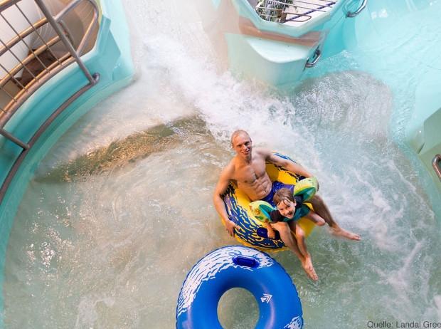 Mann und Kind mit Rutschreifen im Wasser