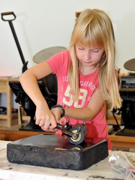 Mädchen bereitet Druckerpresse vor