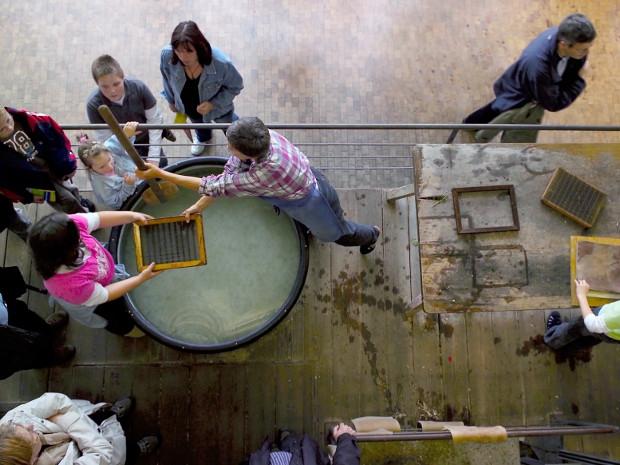 Kinder beim Papierschöpfen