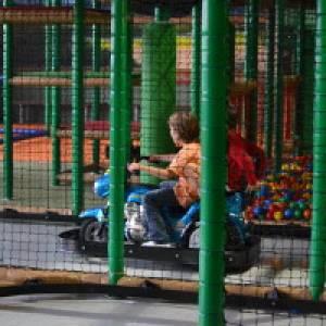 Kinder auf Elektroauto im Indoor-Spielplatz