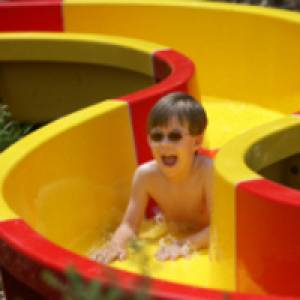 Kind auf rot-gelber Rutsche
