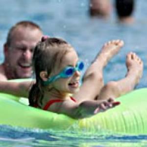 Kind im grünen Schwimmreif im Freibad Mössingen