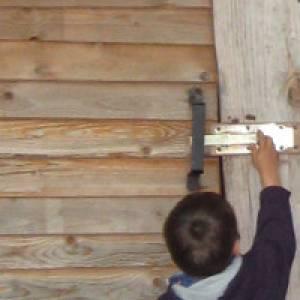 Kind öffnet Holztür